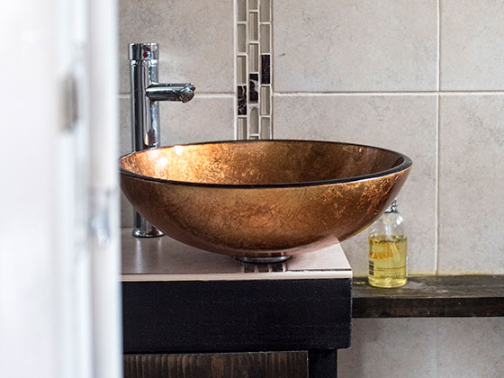 Bespoke bathroom with gold basin in Agricola House